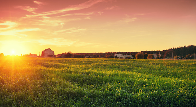 Rural landscape with beautiful gradient evening sky at sunset. Green field and village on horizon